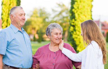 ageing: Happy elderly couple with their carer in the nature