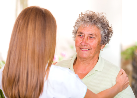reassure: Photo of elderly woman with her caregiver