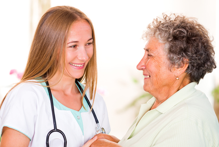 carers: Photo of happy elderly woman with the young doctor Stock Photo