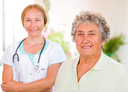 carers: Happy elderly woman with the young doctor  Stock Photo