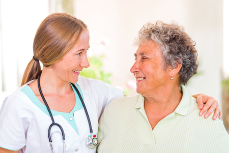 Photo of happy elderly woman with the young doctor photo