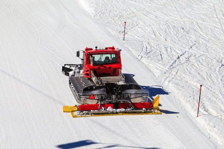snow grooming machine: Photo of a red snowcat in a ski resort