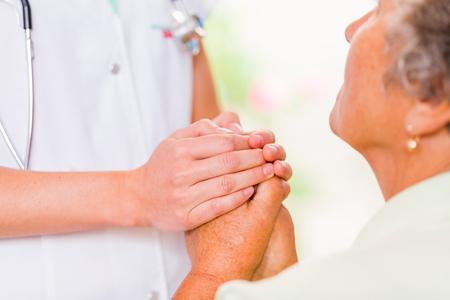 enfermedades mentales: Foto de la joven doctora manos protege las manos de la mujer de edad avanzada