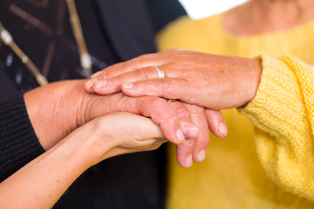 carers: Young doctor holds the old women hands Stock Photo