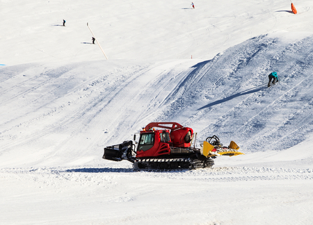 Photo of a red snowcat grooming the ski slope photo
