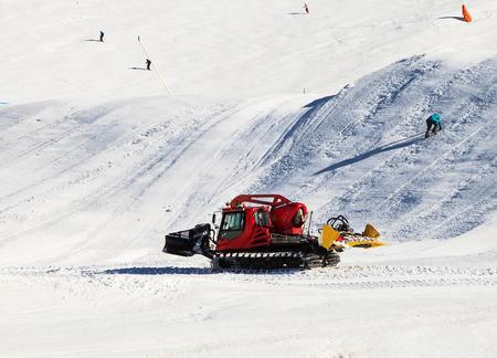 resurfacing: Photo of a red snowcat grooming the ski slope