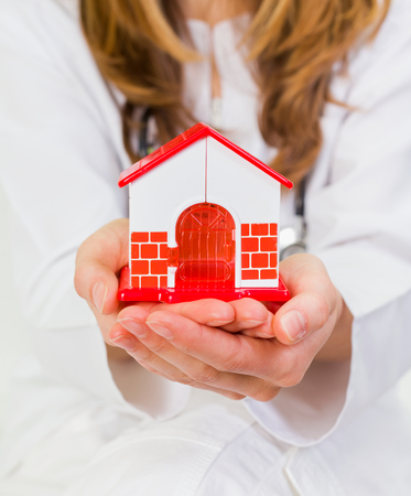 carers: Young woman holds in her hands a plastic house