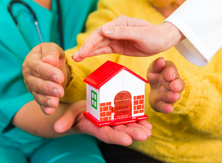 senior carers: Photo of a miniature house holding in hands