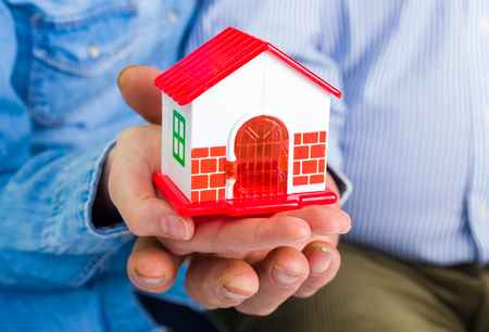 hands holding house: Photo of a miniature house holding in hands