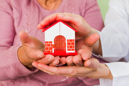 carers: Photo of a toy house protected by hands Stock Photo