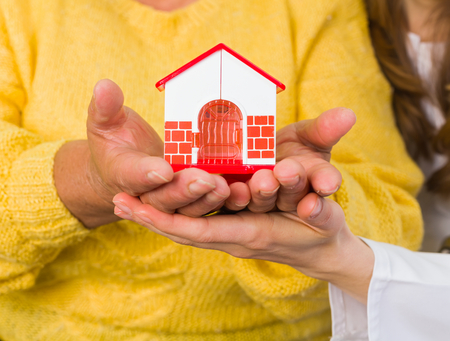 carers: Women holding in hands a miniature house