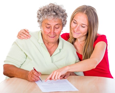 carers: Photo of an elderly woman sign the testament