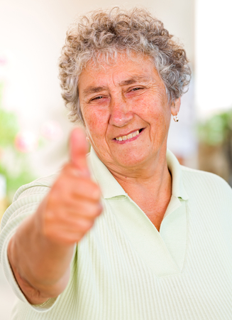 thumbs up woman: Portrait of happy elderly woman shows thumbs up