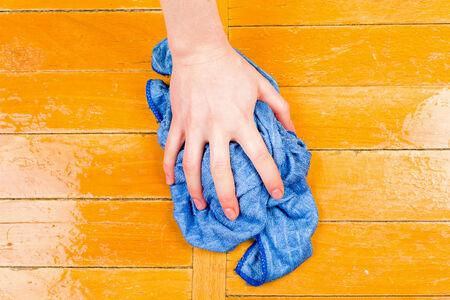 Photo of a hand wash the floor with a rag photo