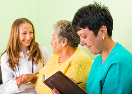 carers: Photo of elderly woman interrogated by the doctor Stock Photo