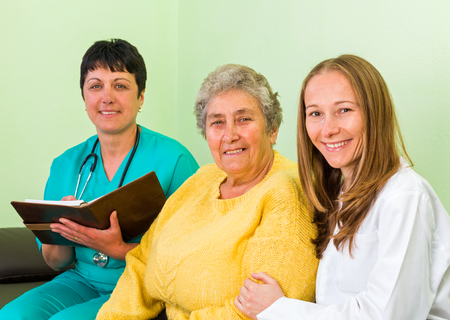carers: Photo of happy elderly woman with her carer and doctor