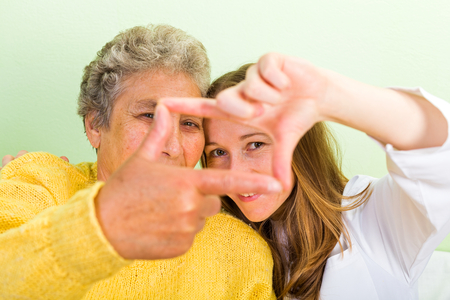 senior carers: Elderly woman and her daughter make frame with their fingers