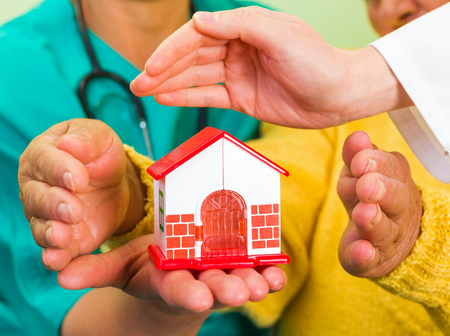 senior carers: a miniature house holding in hands