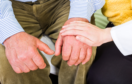 reassurance: Close up photo of elderly man hands and young carer hand Stock Photo