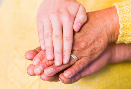 caring hands: Close up photo of elderly woman hands touched by young carer hand Stock Photo