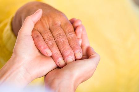 高齢者の女性の手のクローズ アップ写真は若い介護者の手で保持します。