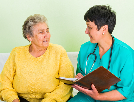 carers: Photo of happy elderly woman with the doctor Stock Photo
