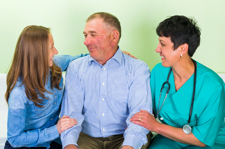 carers: Photo of elderly man with his daughter and doctor Stock Photo
