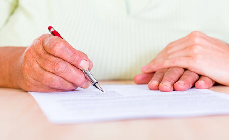 signatory: Photo of an elderly woman sign the testament