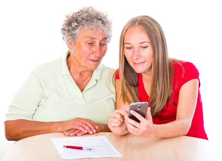 carers: Young girl show how to use the smartphone to her mother