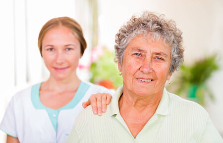 carers: Happy elderly woman with her caregiver in the background