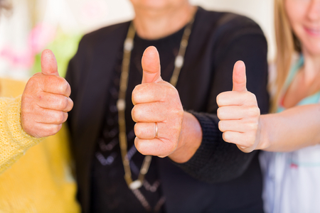 right on: Photo of elderly women with their carer showing thumbs up Stock Photo