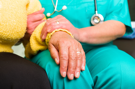carers: Young doctor giving helping hands for elderly woman