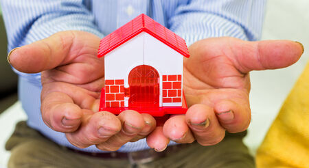 safe house: Photo of a miniature house holding in hands