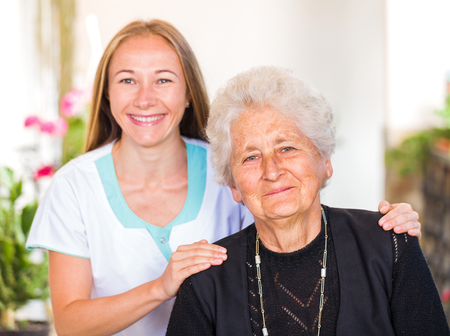 aide: Photo of happy elderly woman with her caregiver