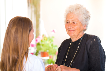 hospice: Photo of young carer holding the elderly woman hands