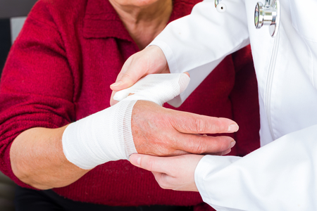 Photo of doctor bandaging the elderly woman thumb