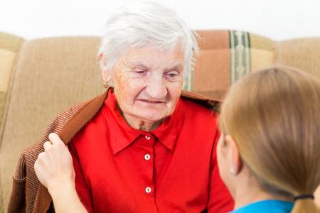 Giovane assistente avvolgere la donna anziana con maglione caldo