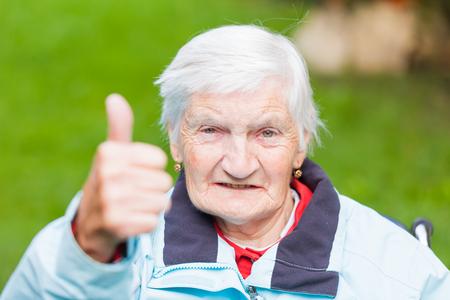 高齢者の女性の肖像画を親指を示しています