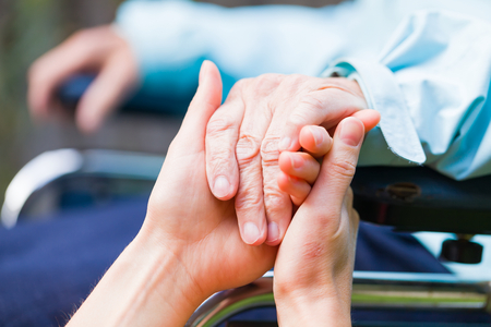 people with disabilities: Young carer giving helping hands for the elderly woman Stock Photo