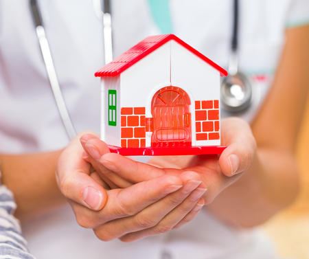 Photo of miniature house holding in young doctor hands Stockfoto