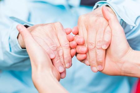 Jeune soignant donnant mains secourables pour la femme âgée Banque d'images