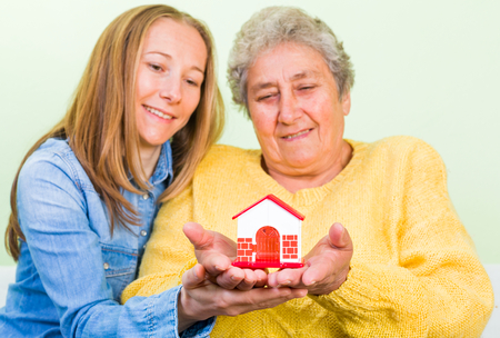 aide: Elderly woman and daughter holding a miniature house in hands