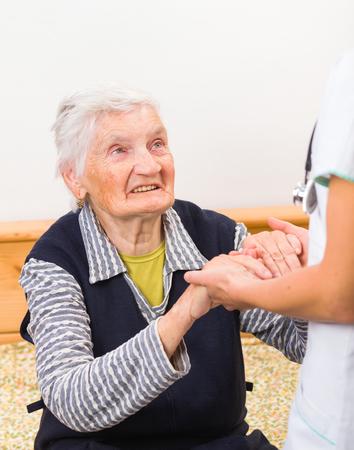 高齢者の女性のための援助の手を与える若い医者 写真素材