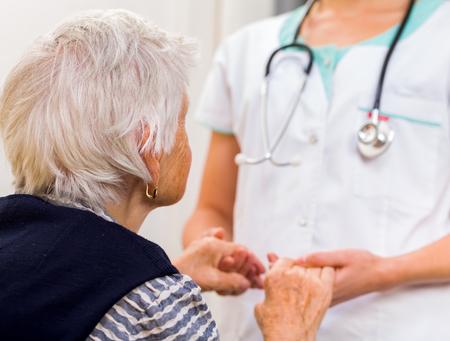 enfermedades mentales: M�dico joven que da la mano de ayuda para la mujer de edad avanzada