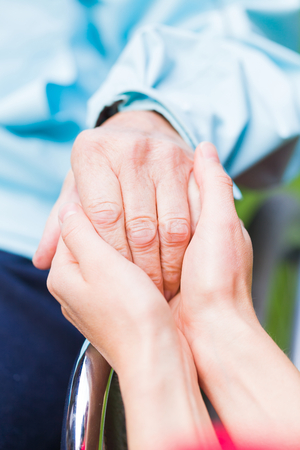 Young carer giving helping hands for the elderly woman Stock Photo
