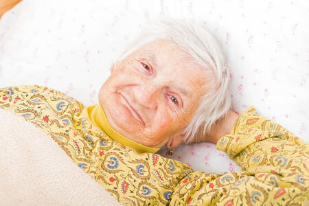 bedridden: Sweet smiling elderly woman resting in bed Stock Photo
