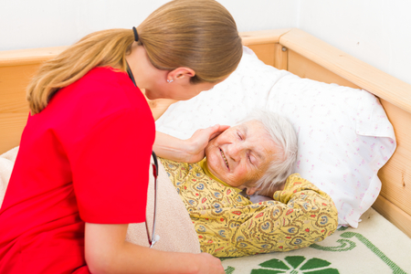 bedridden: Photo of elderly woman with the caregiver