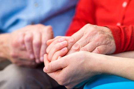Young carer giving helping hands for elderly woman photo