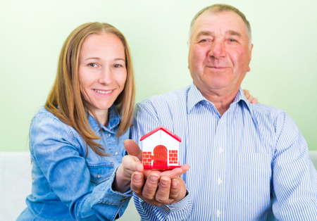 carers: Elderly man and daughter holding a miniature house in hands
