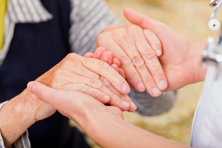 Médico joven que da la mano de ayuda para la mujer de edad avanzada